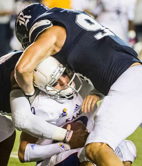 Kansas quarterback Jake Heaps is sacked by Rice defensive end Cody Bauer.