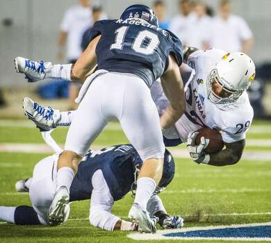 Kansas running back James Sims is upended by Rice linebacker James Radcliffe (10) and safety Malcolm Hill. Photo: Smiley N. Pool, Houston Chronicle
