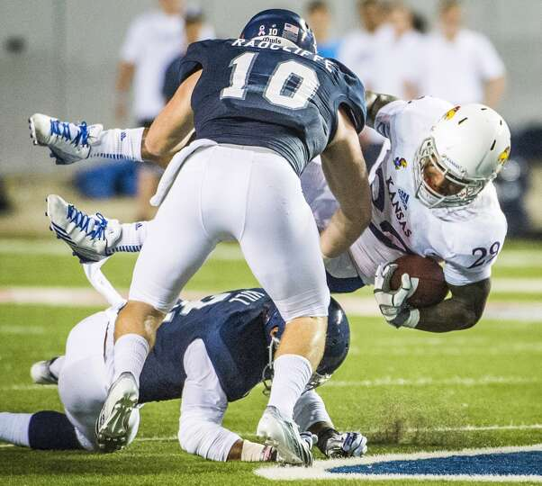 Kansas running back James Sims is upended by Rice linebacker James Radcliffe (10) and safety Malcolm