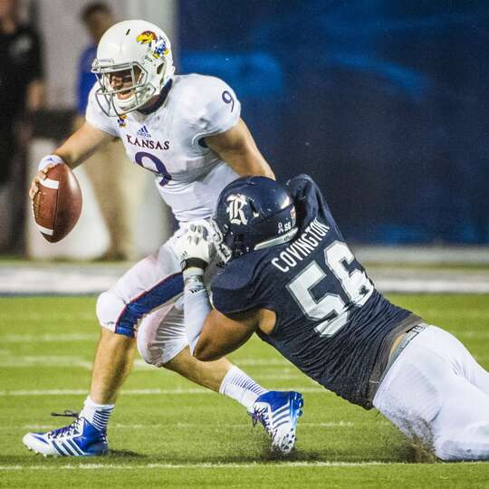 Kansas quarterback Jake Heaps is sacked by Rice defensive tackle Christian Covington.