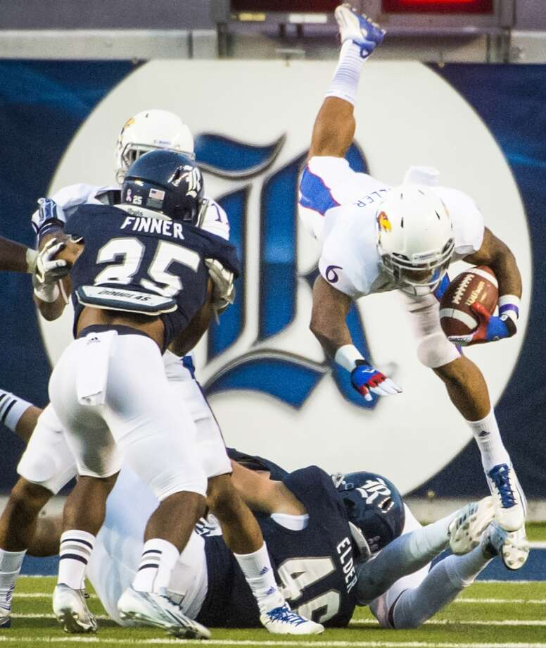 Kansas running back Darrian Miller is upended by Rice linebacker Nick Elder. Photo: Smiley N. Pool, Houston Chronicle