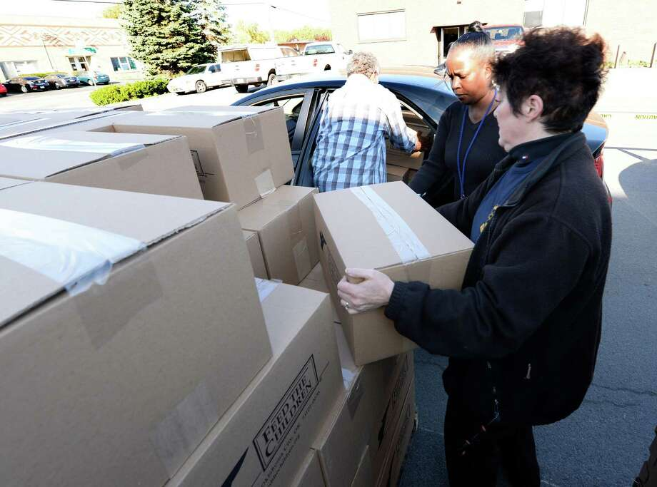 Barbara Wyllie of the Glenville Rotary helps distribute food and personal care products Thrusday morning, Sept. 26, 2013, at the Jerzeel International offices in Colonie, N.Y.  The food distribution was sponsored by Jerzeel International and Americans Feeding Americans and Feed the Children.  (Skip Dickstein / Times Union) Photo: Skip Dickstein / 00023979A