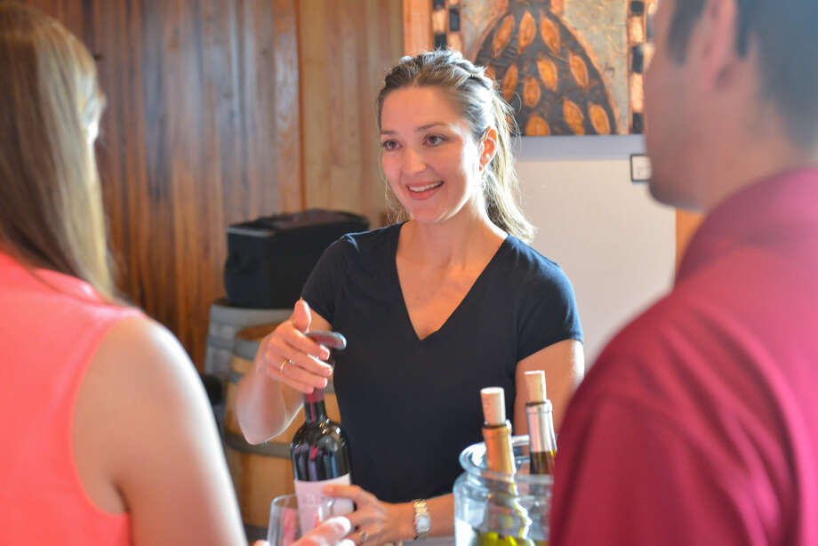 Neldie Hilmy of Hilmy Cellars along the Texas Wine Trail pours a tasting for customers recently.