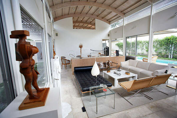The wooden barrel-vault ceiling in the Terrell Hills home of Ken and Carol Bentley was influenced by the Alamo. A sculpture by Phil Evett looks over the living/dining room; other pieces of contemporary art are placed throughout the room, which is bathed in natural light.