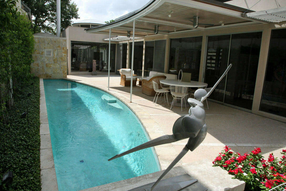 A metal sculpture by Evett appears ready to dive into the lap pool outside.