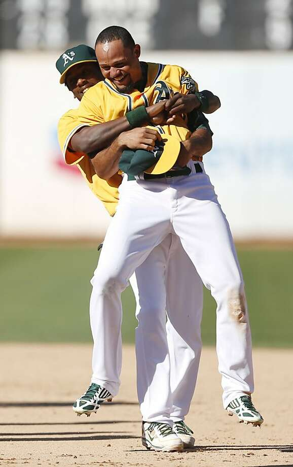 Utilityman Jemile Weeks greets center fielder Coco Crisp with a big hug after the A's clinched the division title Sunday. Photo: Beck Diefenbach, Associated Press