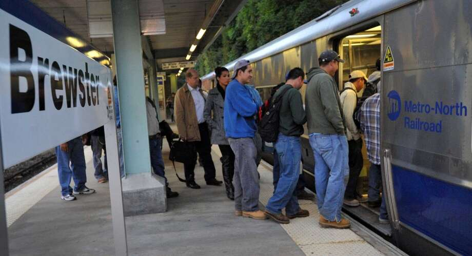 Commuters board an early morning train out of  Brewster, N.Y. for Grand Central Station, Thursday morning, Sept. 26, 2013.  A damaged high-voltage feeder cable affected Metro-North rail service on the New Haven Line for days last fall. Photo: Carol Kaliff