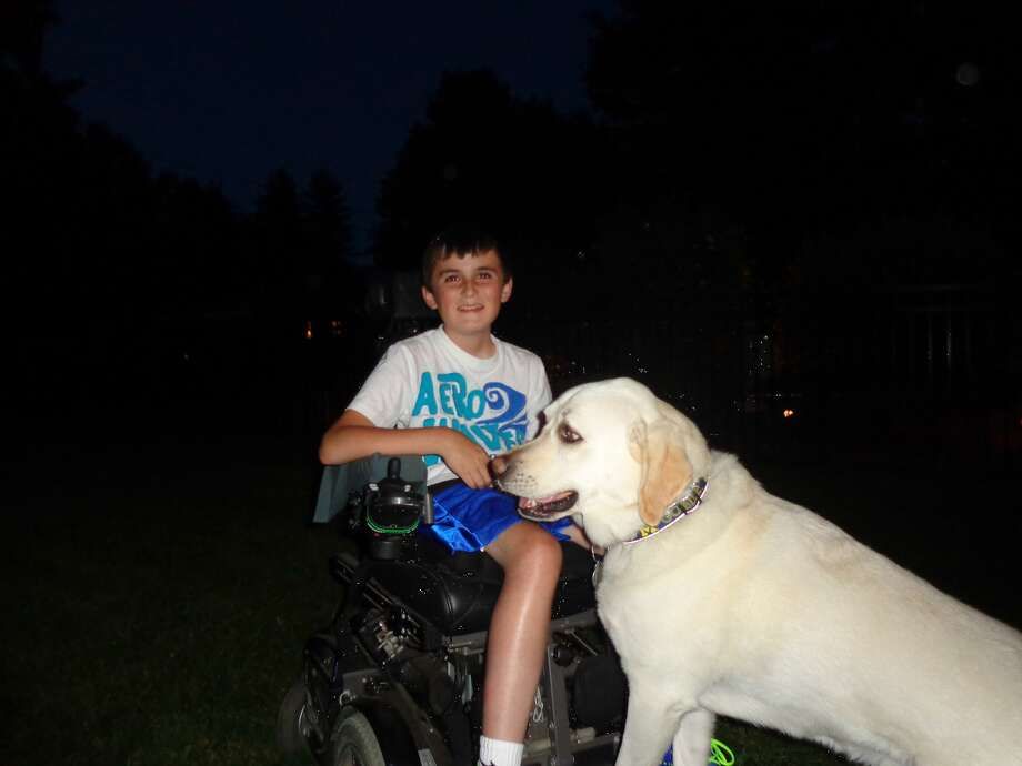 Derek Murphy, 12, poses with his service dog, Matrix. (Linda Long)