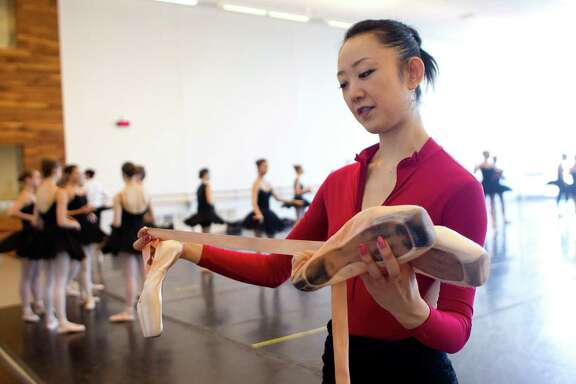 "Holding her pointe shoes she said she could use if she had to defend herself, Nao Kusuzaki, a Houston Ballet company member for about nine years gets ready for a practice at the ballet studio Wednesday, Sept. 25, 2013, in Houston.  Kusuzaki participated in the Houston Police Department's ""Surviving An Active Shooter,"" self-preservation and defense presentation offered by the Houston Ballet. The presentation incorporates the run, hide, fight principles. Kusuzaki said if she had to defend herself she could use her ballet pointe shoes, scissors or a hammer used for conditioning her shoes, which she often keeps with her. ( Johnny Hanson / Houston Chronicle )"