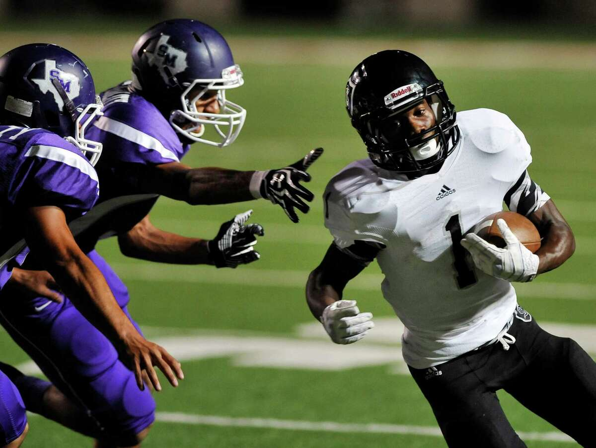 Steele wide receiver Jaylen Harris, right, evades San Marcos defenders and runs for a touchdown during a high school football game, Thursday, Sept. 26, 2013, at Bobcat Stadium in San Marcos, Texas.