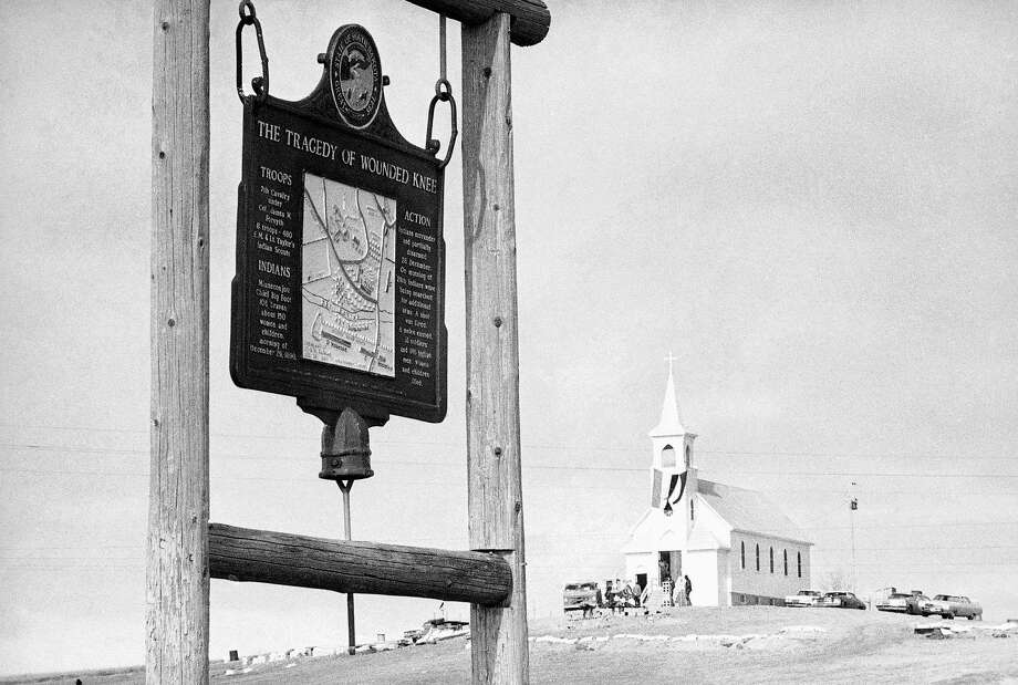In this undated file photo is a  historical marker commemorating the Wounded Knee Massacre of 1890 on the road near the Sacred Heart Catholic Church in Wounded Knee, S.D.  Oglala Sioux President Bryan Brewer plans to meet this week with a Rapid City landowner in what could be a last-ditch attempt to avert the public sale of land near one of the most sacred sites on the Pine Ridge Reservation. Landowner James Czywczynski is accepting sealed bids on the properties until Oct. 15, 2013. If those bids aren't high enough, he said, he plans to put the site up for public auction, possibly as soon as November. Photo: AP