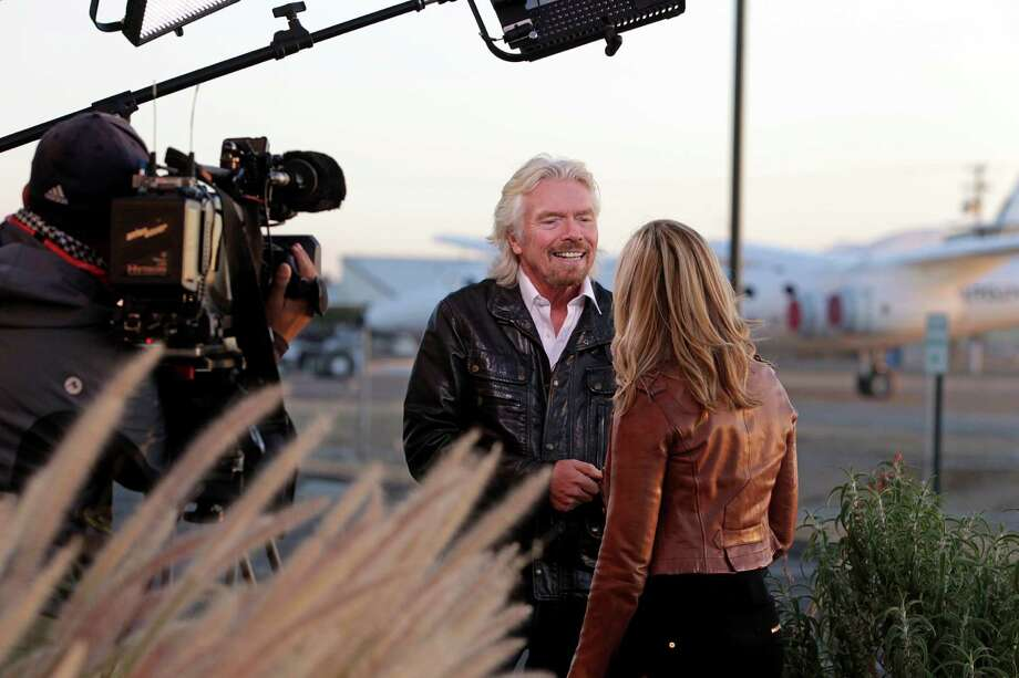 British entrepreneur Richard Branson does a broadcast interview at a Virgin Galactic hangar at Mojave Air and Space Port in Mojave, Calif., Wednesday, Sept. 25, 2013. Potential space tourists gathered in California's Mojave Desert to see the latest progress from Branson's space tourism enterprise. The company has been testing SpaceShipTwo designed to take paying  passengers into space. Commercial flights will begin once testing is complete. Photo: AP