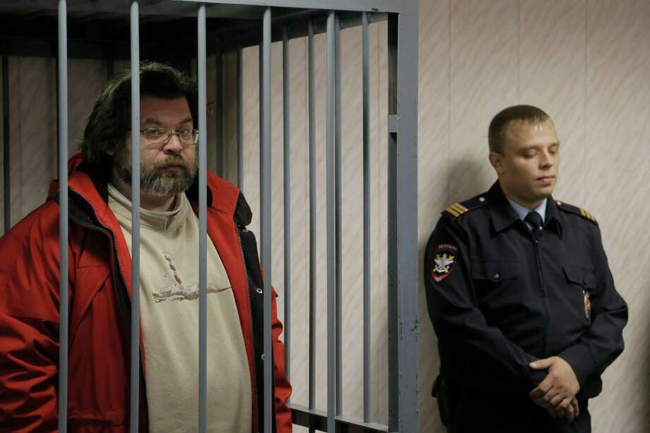 A police officer guards a cage with Greenpeace activist Roman Dolgov, left, in a court room in Murmansk, Russia, on Thursday, Sept. 26, 2013. A Russian court on Thursday jailed Greenpeace arctic project coordinator Roman Dolgov, who was part of the 30-member Greenpeace team protesting near an oil platform last week. Two members of the group were detained Sept. 18 in their attempt to scale the Russian Arctic platform. The Coast Guard seized Greenpeace's ship the next day and towed it with the 30 activists aboard, to Murmansk. The activists are being investigated for piracy. Photo: AP