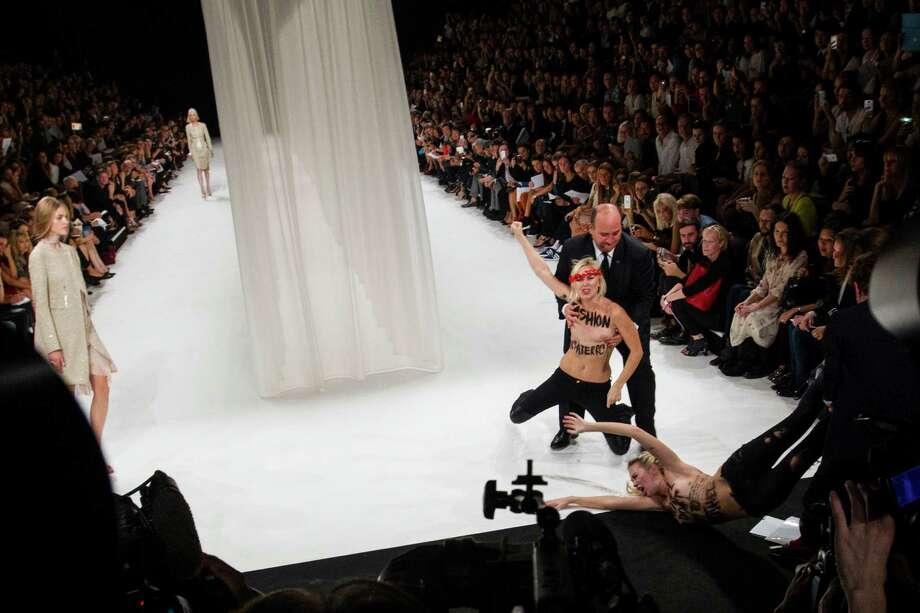 Two activists of Femen, a feminist Ukrainian protest group,  right, are removed by security members while disturbing the presentation of Nina Ricci's ready-to-wear Spring/Summer 2014 fashion collection Thursday, Sept. 26, 2013 in Paris. Photo: AP