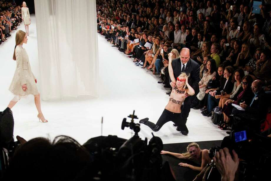 Two activists of Femen, a feminist Ukrainian protest group,  are removed by security staff while disturbing the presentation of Nina Ricci's ready-to-wear Spring/Summer 2014 fashion collection Thursday, Sept. 26, 2013 in Paris. Photo: AP