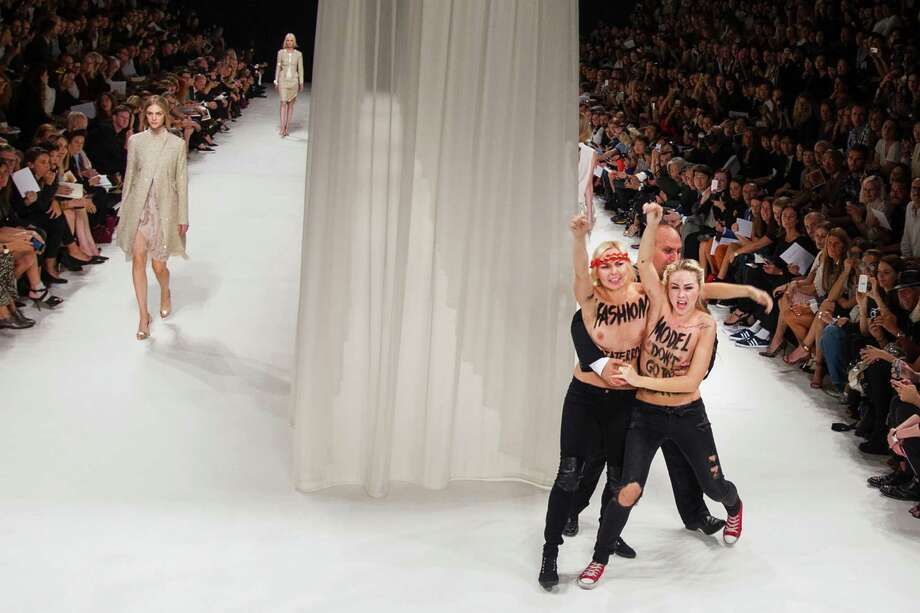 Two Femen activists, right, are evacuated by a security member while disturbing the presentation of Nina Ricci's ready-to-wear Spring/Summer 2014 fashion collection Thursday, Sept. 26, 2013 in Paris. Photo: AP