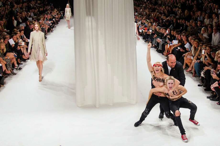 Two Femen activists, right, are removed by a security member while disturbing the presentation of Nina Ricci's ready-to-wear Spring/Summer 2014 fashion collection Thursday, Sept. 26, 2013 in Paris. Photo: AP