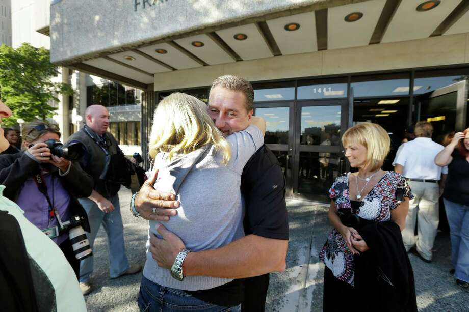 Thomas Highers is hugged after leaving Wayne County Circuit Court in Detroit a free man on Thursday, Sept. 26, 2013. Murder charges that put Thomas and his brother Raymond Highers behind bars for 25 years were dismissed. Circuit Judge Lawrence Talon formally dismissed the murder charges against the brothers on Thursday, a day after Wayne County Prosecutor Kym Worthy announced she wouldn't be retrying the men for the 1987 slaying of 65-year-old Robert Karey. Photo: AP