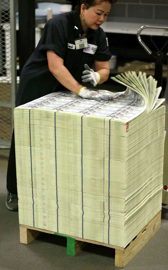 A stack of uncut sheets of $100 bills are inspected before being moved during the printing process at the Bureau of Engraving and Printing Western Currency Facility in Fort Worth, Texas, Tuesday, Sept. 24, 2013.  The federal printing facility is making the new-look colorful bills that include new security features in advance of the Oct. 8 circulation date. Photo: AP