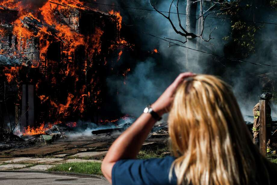 An area resident watches on as Flint firefighters battle a blaze that engulfed a vacant house on Flint's north side Tuesday, Sept. 24, 2013 at about 3:30 p.m. on Paterson Street near Francis Avenue. Photo: AP