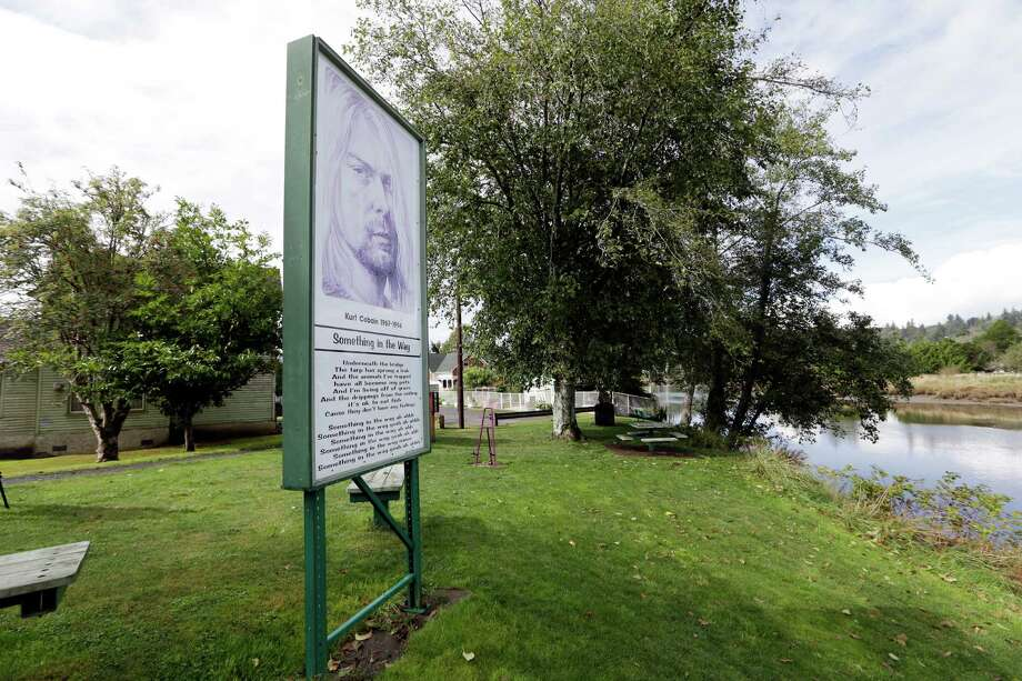 "In this photo taken Monday, Sept. 23, 2013, a sign marks the location of ""Kurt Cobain Landing,"" a small park blocks from the childhood home of Kurt Cobain, the late frontman of Nirvana, and overlooking the Wishkah River in Aberdeen, Wash. Cobain's mother is putting the tired, 1.5-story Aberdeen bungalow on the market this week, the same month as the 20th anniversary of Nirvana's final studio album. The home, last assessed at less than $67,000, is being listed for $500,000, but the family would also be happy entering into a partnership with anyone who wants to turn it into a museum. Photo: AP"