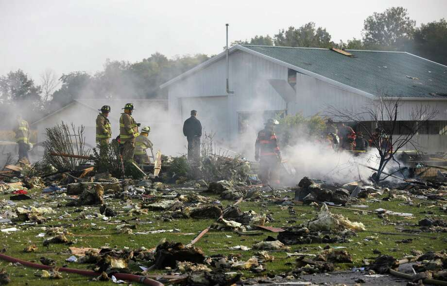 Firefighters search through debris after an explosion at a home near Liberty Center, Ohio, Wednesday, Sept. 25, 2013. Authorities say the explosion killed a woman and injured a man. (AP Photo/The Blade, Dave Zapotosky)  Photo: AP
