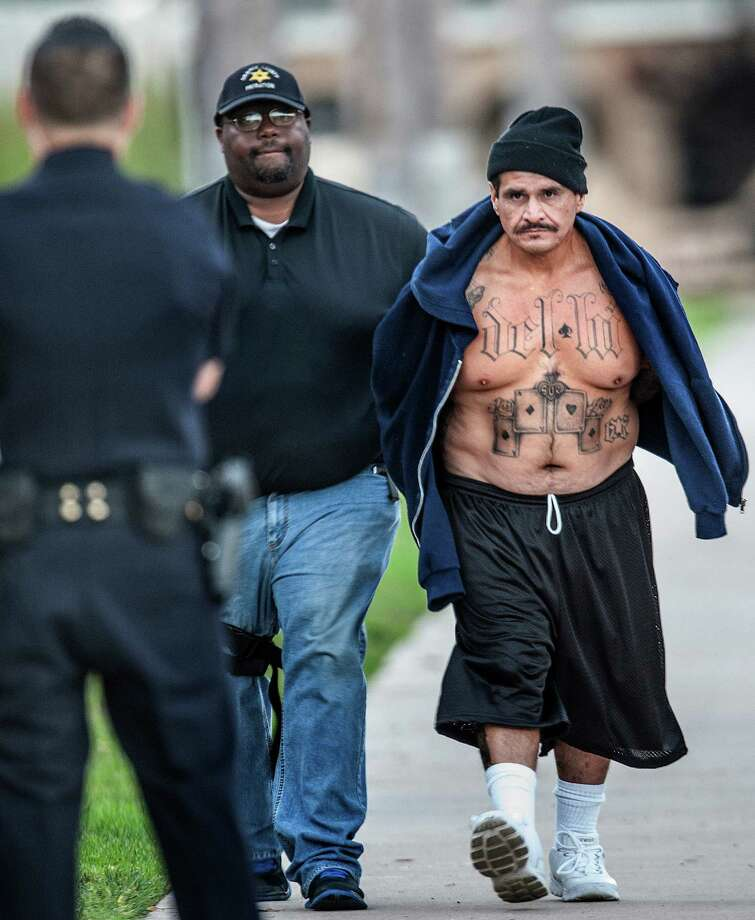 A man arrested during an early morning gang sweep is walked to the Santa Ana Police Department for booking Tuesday Sept. 24, 2013, in Santa Ana, Calif.  More than 120 people linked to street gangs that claim allegiance to the Mexican Mafia have been indicted on various racketeering, weapons and narcotics charges.    (AP Photo/The Orange County Register, Bruce Chambers)  Photo: AP