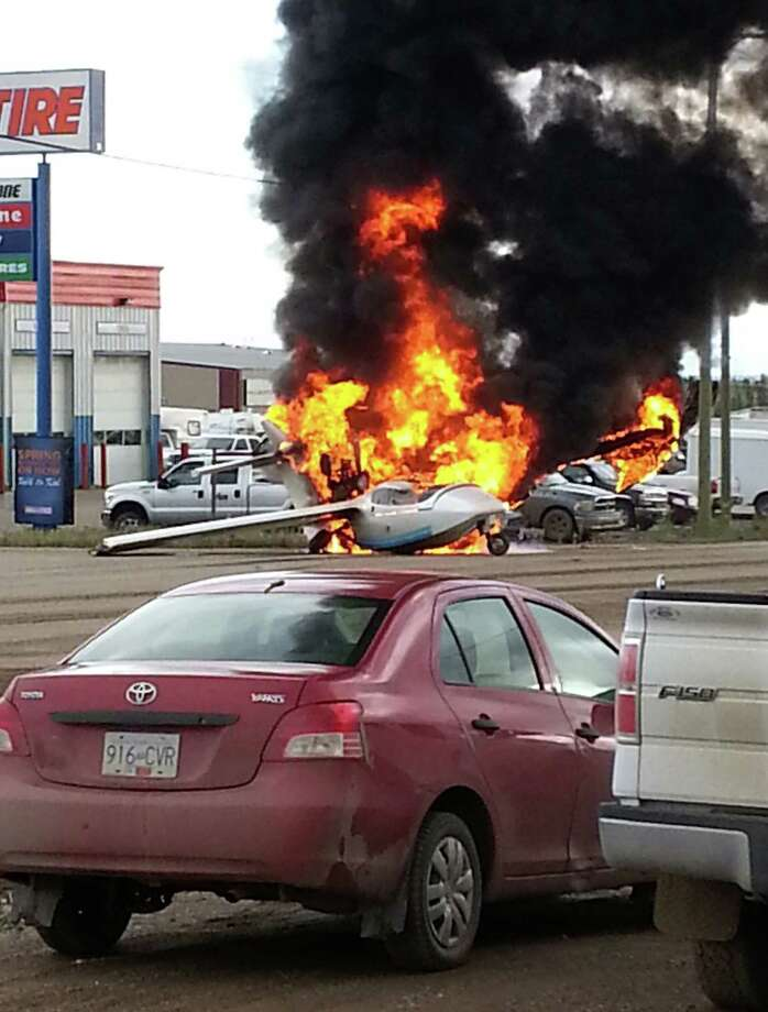 A plane is engulfed in flames in the middle of an intersection in Fort Nelson, British Columbia on Wednesday, Sept. 25, 2013. Police in British Columbia say a pilot suffered only minor injuries. Photo: AP