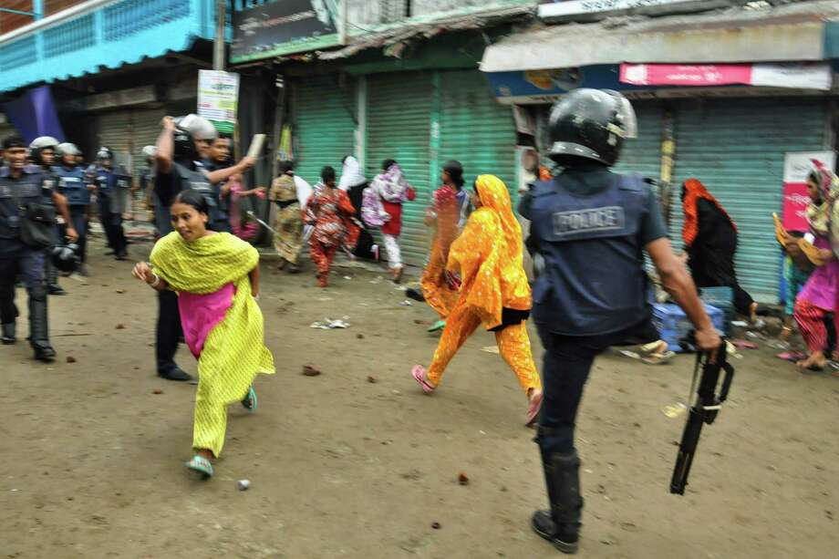 Bangladeshi garment workers run as police disperse them during a protest march in Narayanganj, near Dhaka, Bangladesh, Wednesday, Sept. 25, 2013. The fifth day of protests Wednesday by workers demanding higher wages in two industrial districts near Dhaka forced authorities to close more than 100 factories for the day. Bangladesh earns $20 billion a year from garment exports. Photo: AP