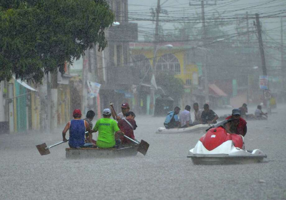 Residents use small boats and jet skis to evacuate and remove their belongings from flooded areas during heavy rain in the town of Titxla de Guerrero, Mexico, Tuesday, Sept. 24, 2013. The area, already hard hit by last week's Tropical Storm Manuel, continues to be battered by heavy rain. Photo: AP