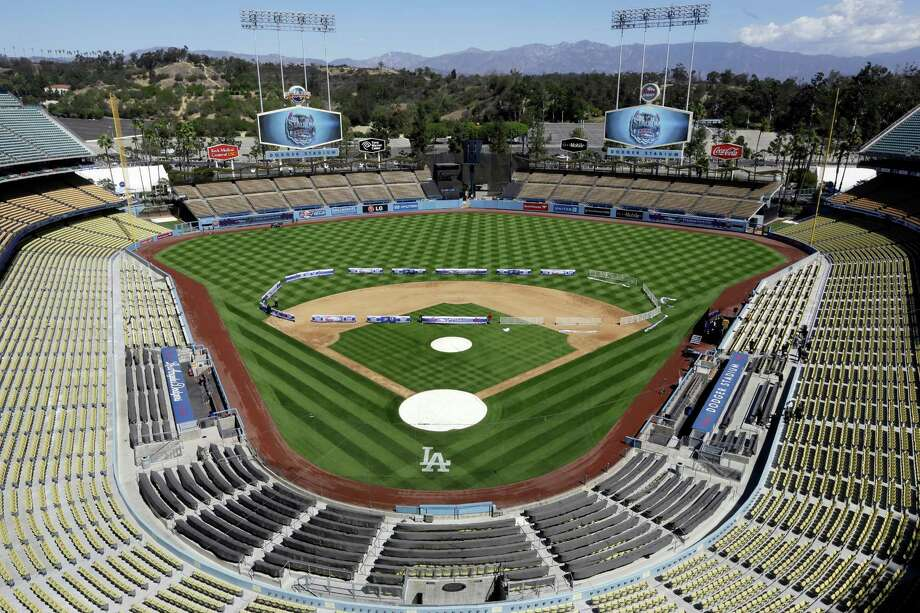 Workers install banners in the shape of a hockey rink at Dodger Stadium before an NHL news conference Thursday to announce an outdoor hockey game there between the Kings and Ducks on Jan. 25. Photo: Damian Dovarganes, STF / AP