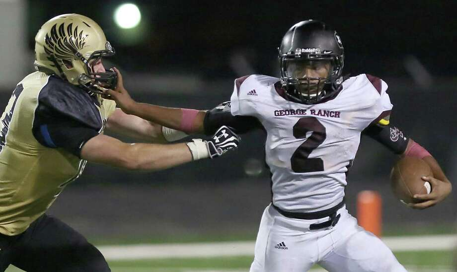 George Ranch quarterback Timon Nolan, right, tries to keep Foster's Bradley Mbu at arm's length as he picks up yardage in Thursday night's District 23-4A opener. Nolan rushed for 137 yards and three touchdowns on 21 carries. Photo: Thomas B. Shea / © 2013 Thomas B. Shea