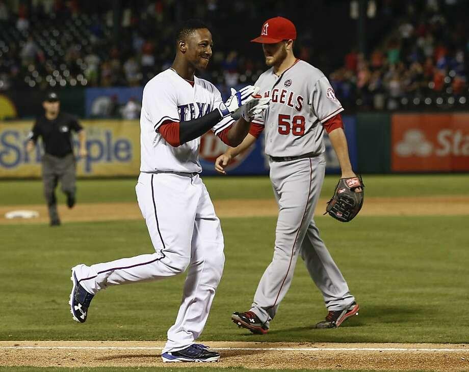 Texas' Jurickson Profar circles the bases after his game-winning home run of Michael Kohn. Photo: Jim Cowsert, Associated Press