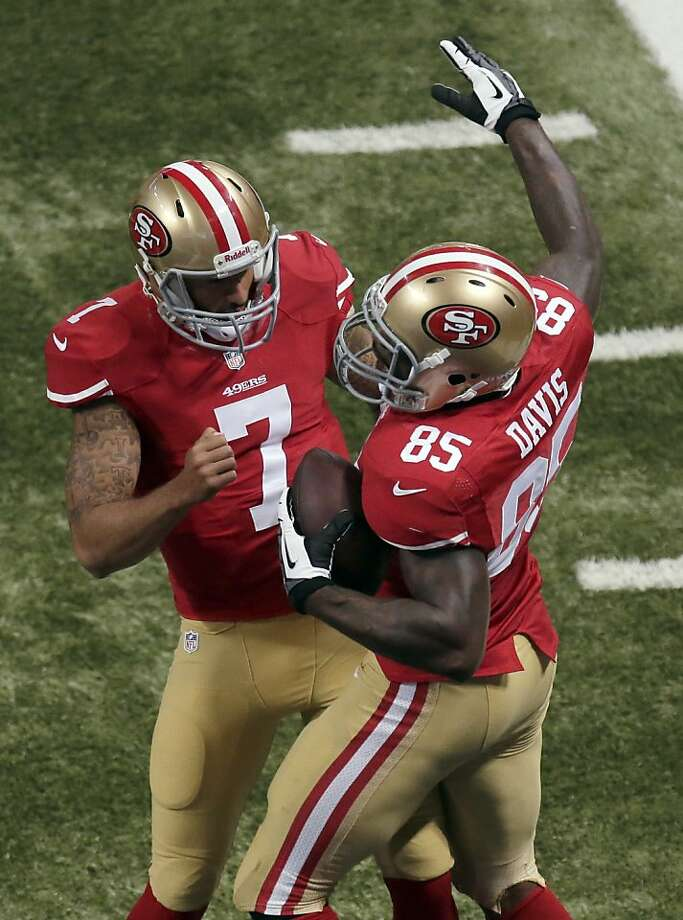 Colin Kaepernick (left), who threw a scoring pass to Vernon Davis, benefited from Frank Gore's re-emergence. Photo: Charlie Riedel, Associated Press