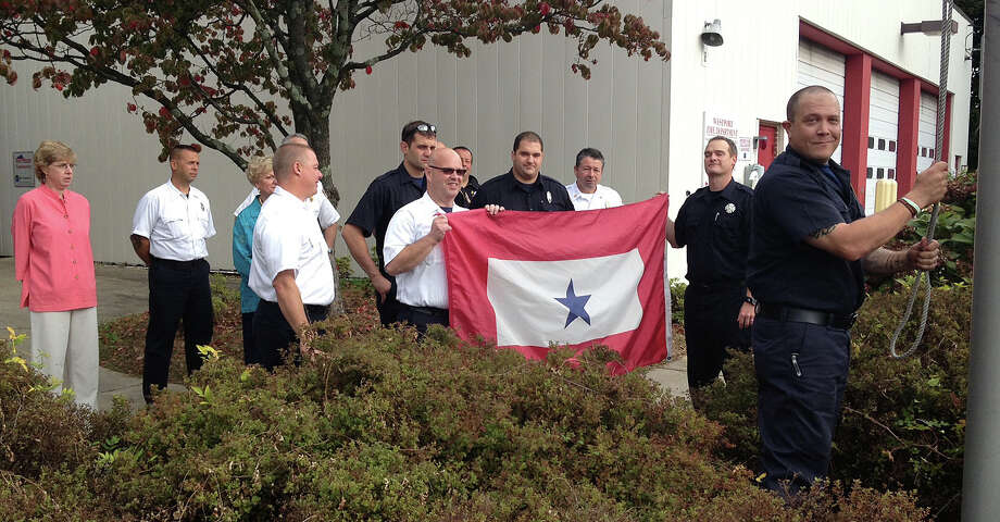 Firefighter Pete Nichio, who recently returned to duty after a year's deployment in Afghanistan, was welcomed back with a ceremony during which a  Blue Star Service Flag flown during Nichio's absence was taken down. Photo: Westport Fire Department / Westport News contributed