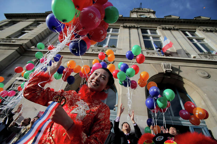 A woman releases balloons during the Chinese Moon Festival also known as the Mid-Autumn Festival in Paris, on Thursday, Sept. 19, 2013. The Mid-Autumn Festival falls on the 15th day of the 8th lunar month of the Chinese calendar and is marked by Chinese families and friends gathering to eat Chinese mooncakes together. Photo: Christophe Ena, AP / AP