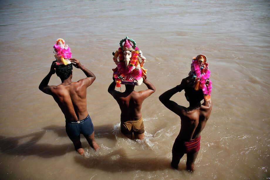 Indian devotees prepare to immerse idols of elephant-headed Hindu god Ganesha in the Chenab River during Ganesh Chaturthi festival celebrations in Akhnoor, India, Monday, Sept. 16, 2013. The festival is celebrated to mark the birth of Ganesha, the Hindu god of wisdom, prosperity and good fortune. Photo: Channi Anand, AP / AP