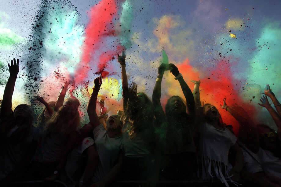 Revelers throw colored powders in the air during the Holi Festival of Colors in Lisbon, Sunday, Sept. 15, 2013. The festival, which is mainly celebrated during the Hindu spring festival Holi in some regions of India and Nepal, has become popular among people in other communities. Photo: Francisco Seco, AP / AP