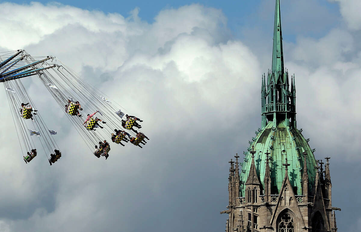 People ride a swing in front of the St. Paul's church at the opening day of the Bavarian Oktoberfest beer festival in Munich on Saturday, Sept. 21, 2013. The world's largest beer festival, held Sept. 21-Oct. 6, is expected to attract more than six million guests from around the world.