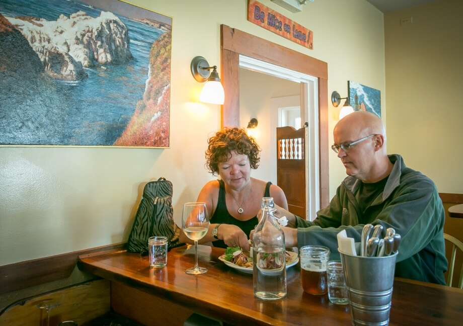 A couple has drinks and food at Rocker Oysterfeller's In Valley Ford. Photo: John Storey, Special To The Chronicle