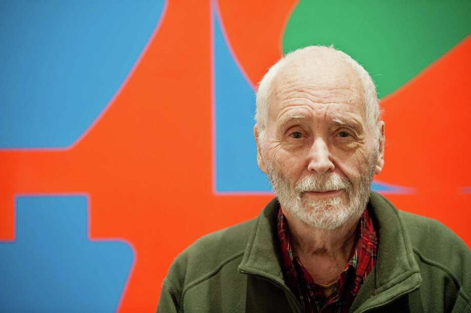 "In this Sept. 24, 2013 photo, artist Robert Indiana, known world over for his LOVE image, is interviewed in front of that painting at New York's Whitney Museum of American Art. Surrounded by 95 works he created over the past five decades, Indiana, who turned 85 this month, calls the retrospective ""a dream come true, a little late."" (AP Photo/Lauren Casselberry) Photo: Lauren Casselberry, STR / AP"