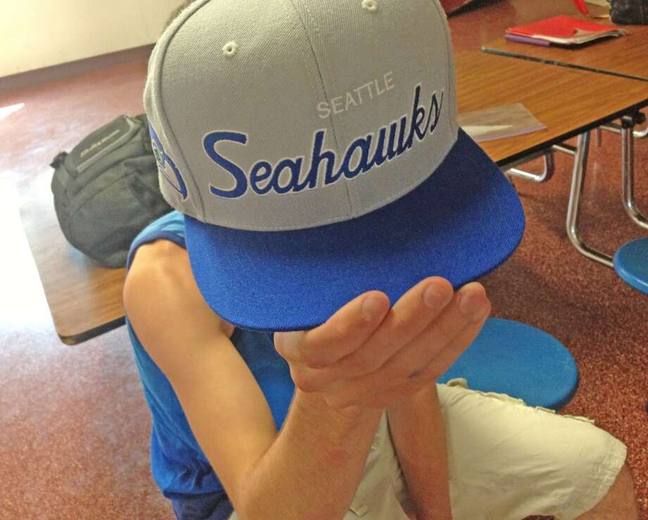 "Collin Goodman, 16 at Berne-Knox-Westerlo holding up his blue and gray ""Seattle Seahawk"" snapback. Photo: Audrey Goodemote"