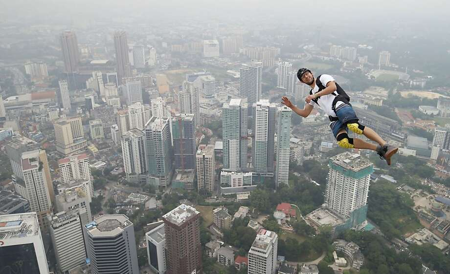 See you in the lobby:BASE jumper Kristian Moxnes of Norway leaps from the 300-meter Open Deck of Malaysia's landmark Kuala Lumpur Tower. About 100 professional BASE jumpers from 20 countries took part in the city's annual International Tower Jump. Photo: Vincent Thian, Associated Press