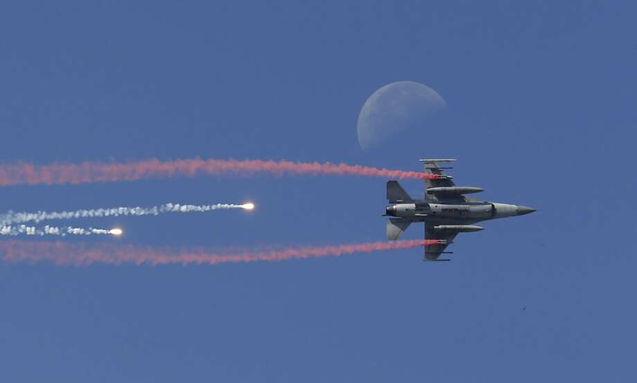 Air show-off: A South Korean Air Force F-16 fighter fires flares as it soars under a half moon during Armed Forces Day at Seoul military airport. Photo: Lee Jin-man, Associated Press