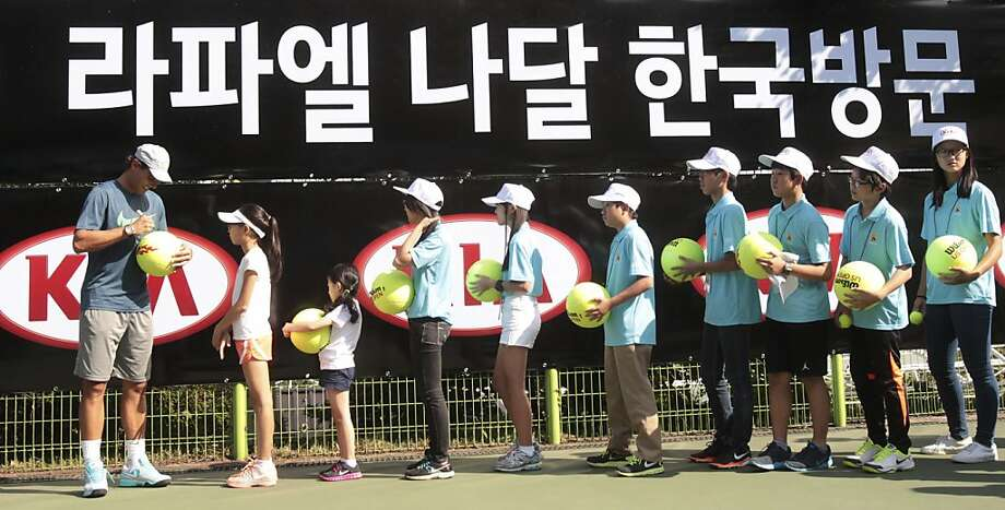 You have to have big ballsto ask for Rafael Nadal's autograph in Seoul. (It's hard to fit his flamboyant signature on a regulation tennis balls.) Photo: Ahn Young-joon, Associated Press