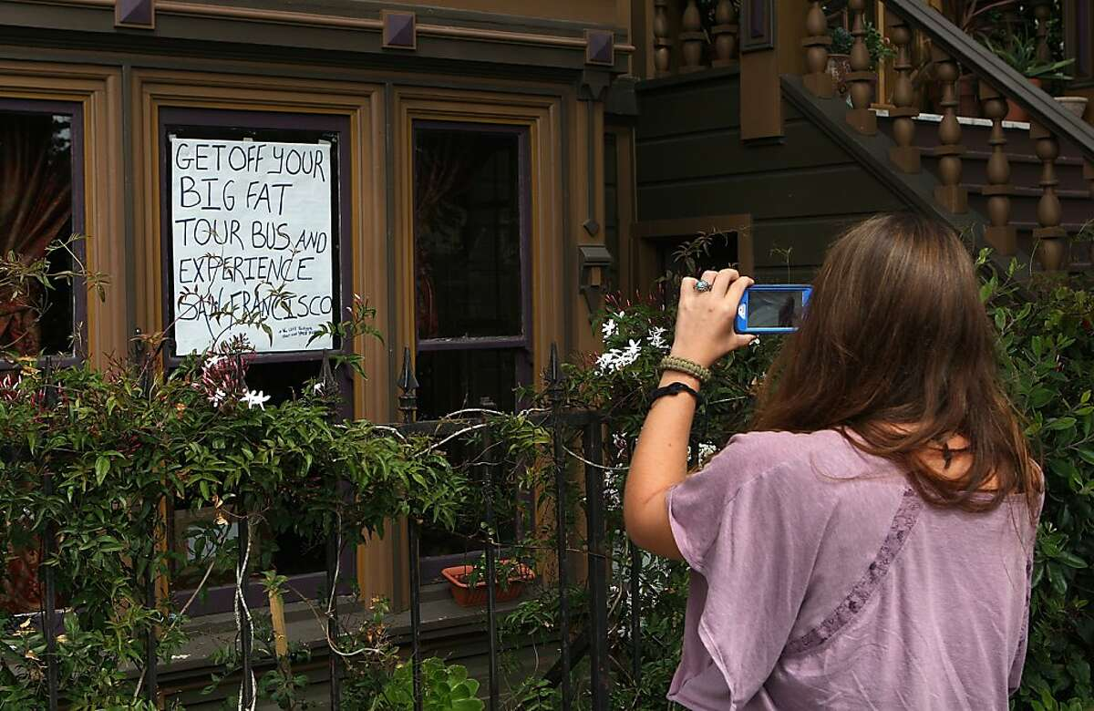 Neighbor Kelly Edwards has a sign in his window concerning tour buses visiting the painted ladies next to Alamo Square in San Francisco, California, on Friday, September 20, 2013. A tourist takes a picture of it while passing by.
