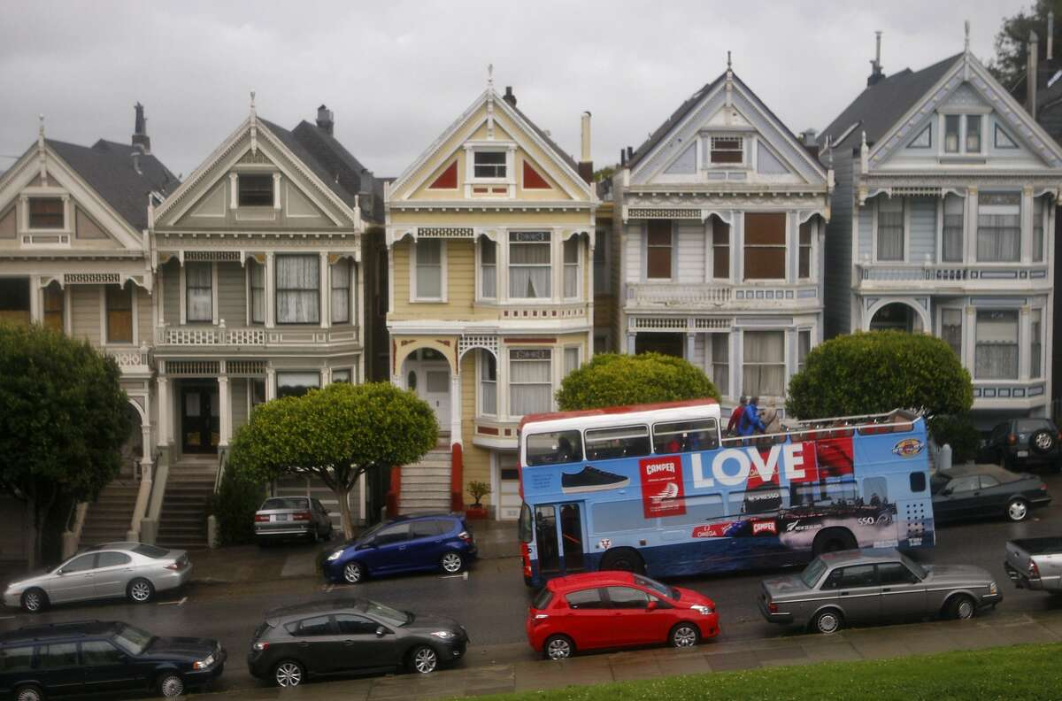 A tour bus passes the painted ladies and Alamo Square Park along Steiner st in San Francisco, Saturday, Sept. 21, 2013.
