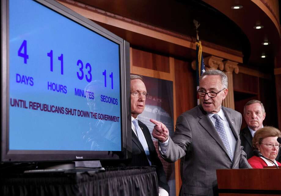 With four days to go before the federal government is due to run out of money, Sen. Charles Schumer, D-N.Y., center, points to a countdown clock during a news conference on Capitol Hill in Washington, Thursday, Sept. 26, 2013, as Senate Democratic leaders blame conservative Republicans for holding up a stopgap spending bill to keep the government running. From left are, Senate Majority Leader Harry Reid of Nev., Schumer, Senate Majority Whip Richard Durbin of Ill., and Senate Appropriations Committee Chair Sen. Barbara Mikulski, D-Md. Photo: J. Scott Applewhite