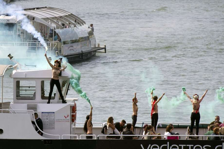 Activists of Ukrainian feminist movement Femen hold flares on a fly boat on the Seine river during a protest in support of 22 crew members  of a Greenpeace ship in pre-trial detention in Russia, on September 27, 2013 in Paris. Photo: FRED DUFOUR, AFP/Getty Images