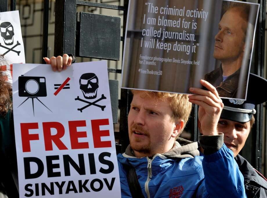 A Ukrainian journalist holds signs calling for the release of photographer Denis Sinyakov during a protest outside the Russian embassy in Kiev on September 27, 2013. A Russian court ordered two Greenpeace International activists, the contracted freelance photographer Denis Sinyakov and the expert Roman Dolgov, both Russian citizens, to be detained for two months over a protest on an Arctic oil platform, as the Netherlands called for the activists' immediate release and threatened legal action against Moscow. Photo: SERGEI SUPINSKY, AFP/Getty Images